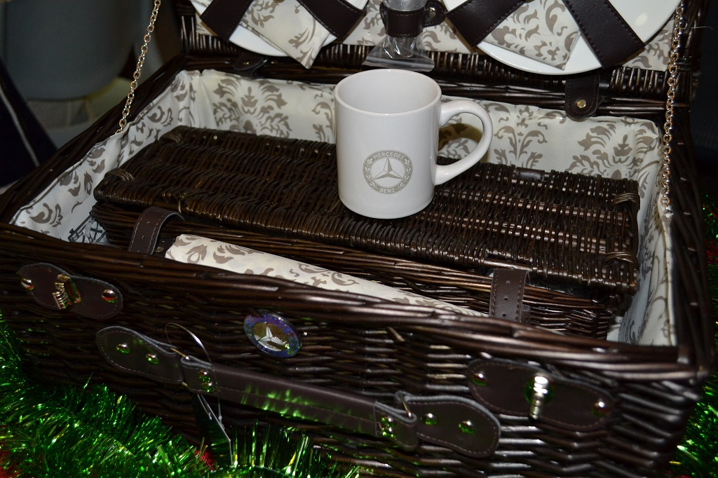 The willow basket contains porcelain mugs & plates, stainless steel cutlery and a matching table cloth.