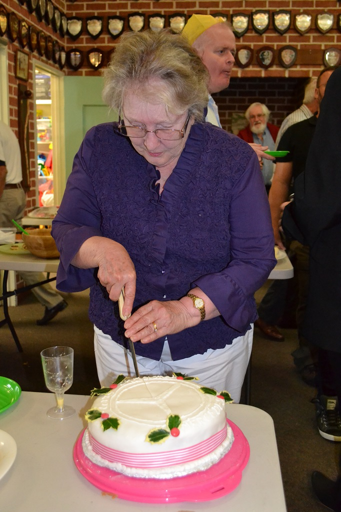 Shirley Hall cutting the cake, signifying the start of the Christmas season and the end of the club's events for the year